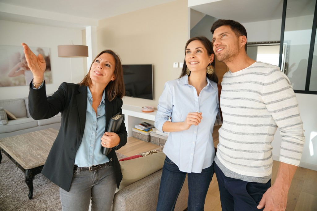 Real estate agent and clients visiting a house