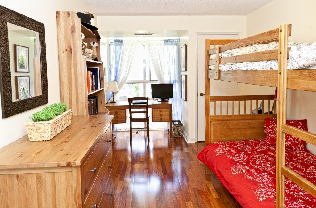 A bedroom with hardwood floors and bunk bed