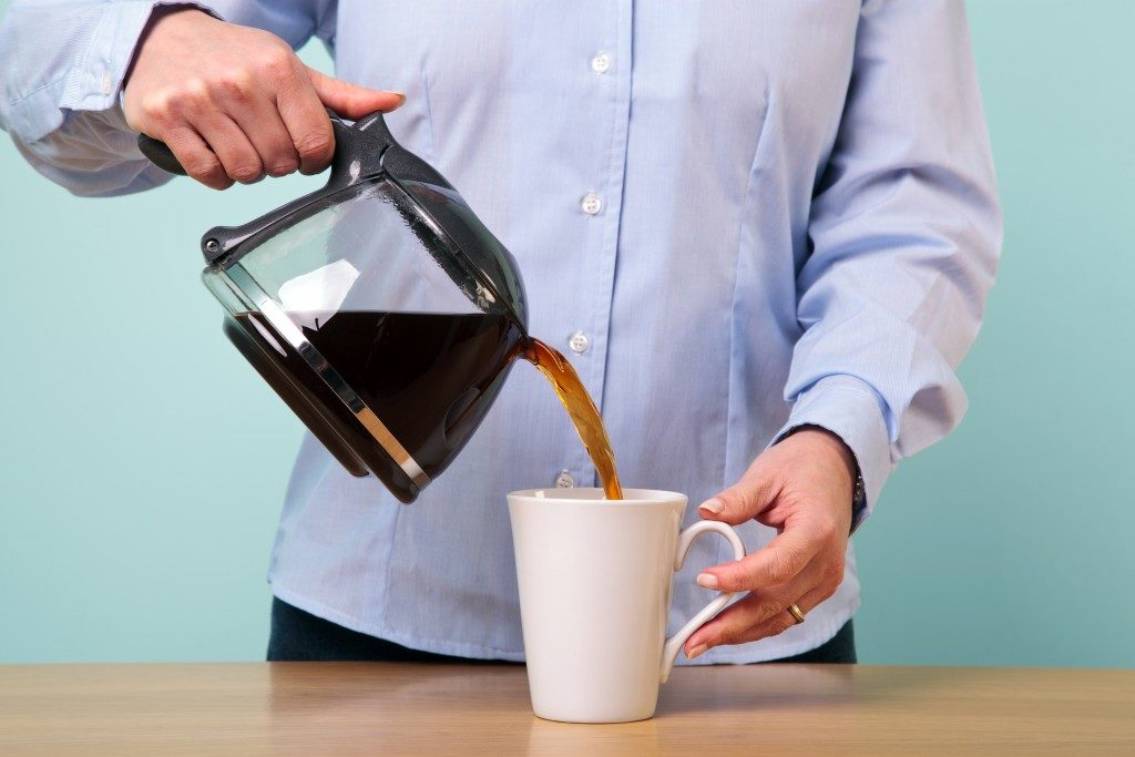 woman on her break pouring herself a mug of hot filtered coffe