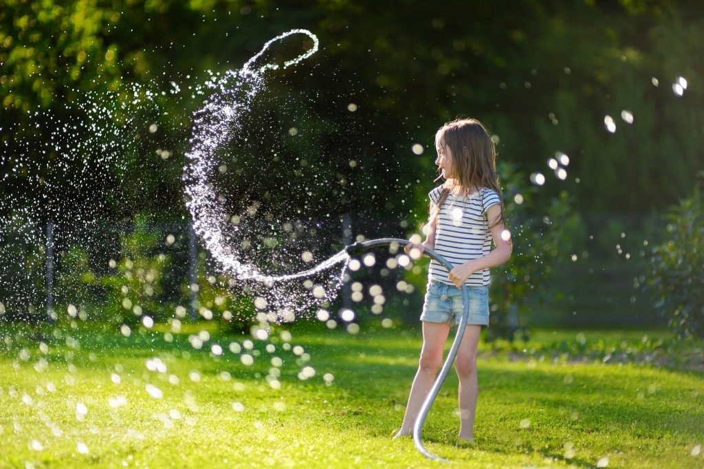 kid playing water hose