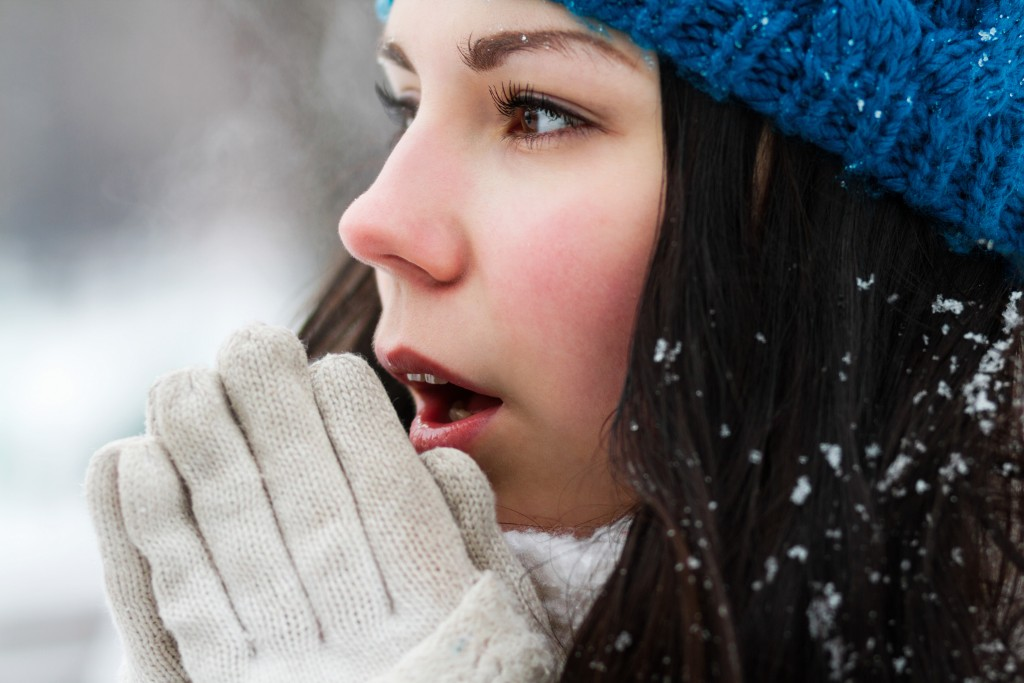 Young woman breathe with warm air on her frozen hands