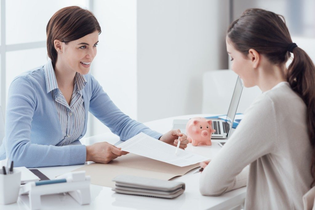 Financial adviser showing insurance policy to client