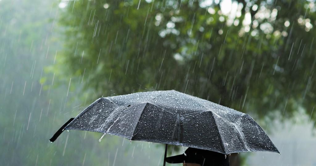 A person holding an umbrella under heavy rain