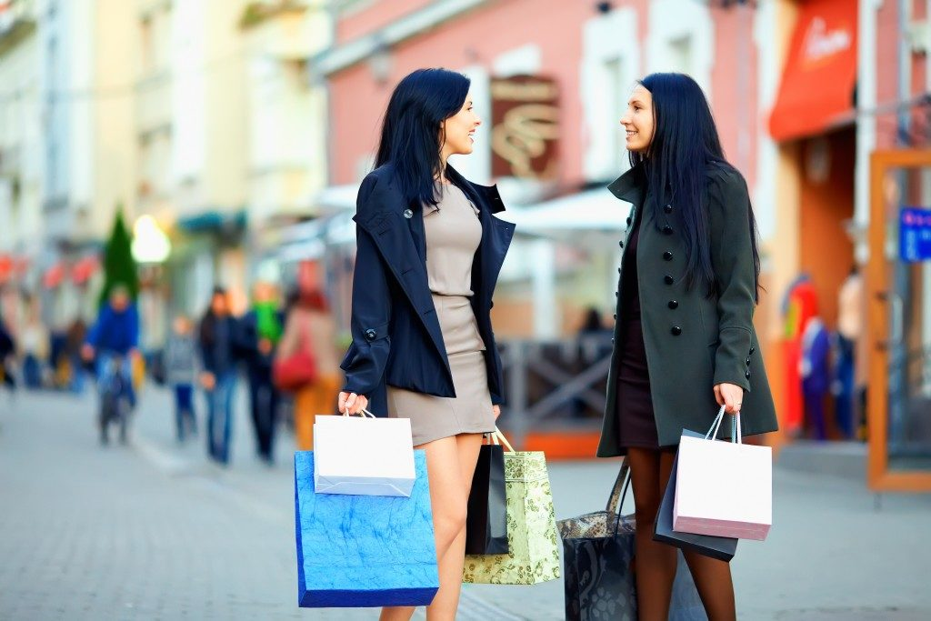 two women walking along street with shopping bags