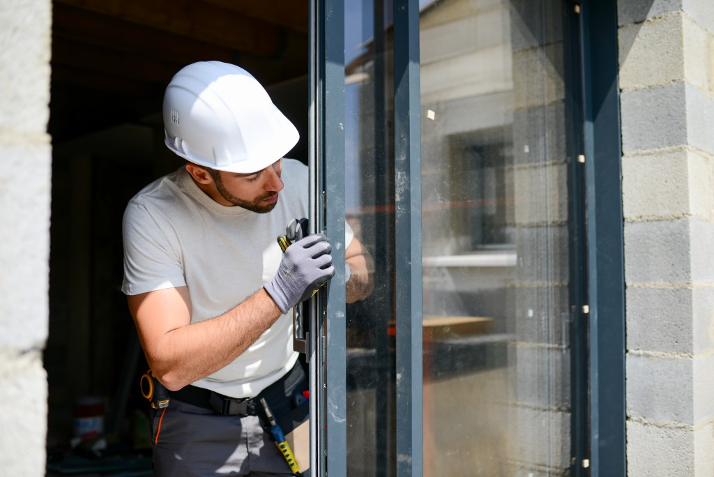 Man adjusting window frame