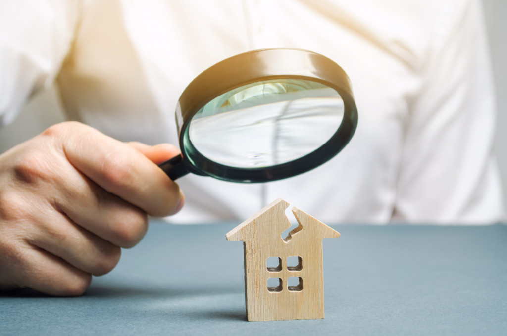 man with a magnifying glass looks at a house with a crack
