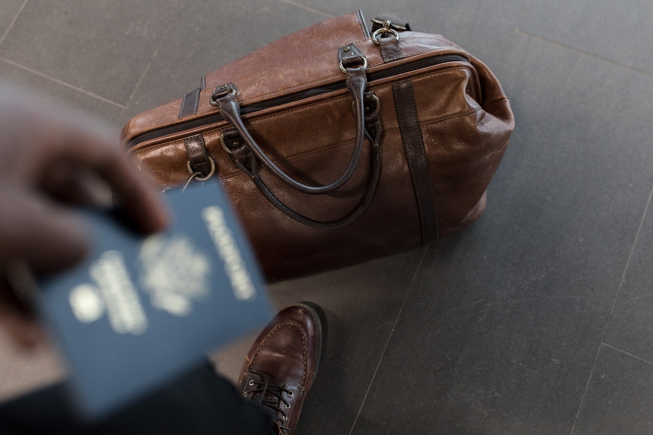 a duffle bag next to someone holding a passport