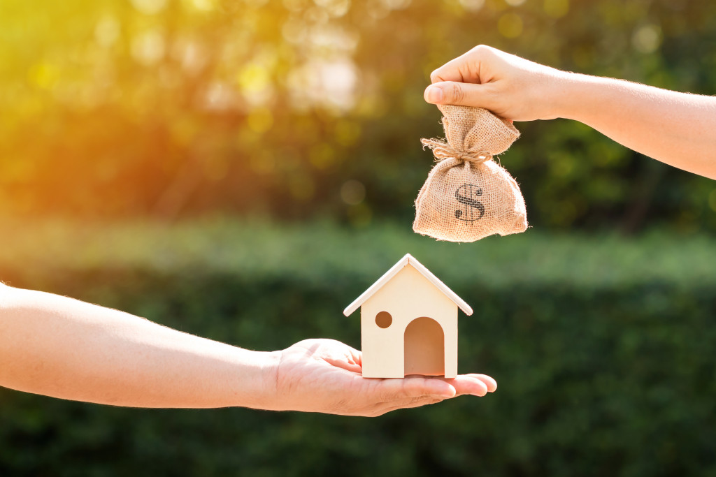 one hand holding a wooden house figure and a hand holding a pouch of money