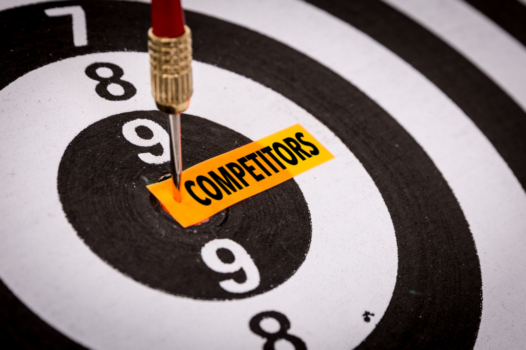 """the word """"competitors"""" written on a yellow paper pinned to a dartboard"""